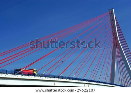Suspension bridge over the Martwa Wisla in Gdansk, Poland with truck and blue sky.