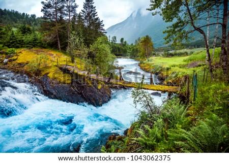 Suspension bridge over the mountain river. Beautiful Nature Norway natural landscape.