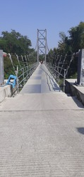 suspension bridge over the river supported by hefty wire