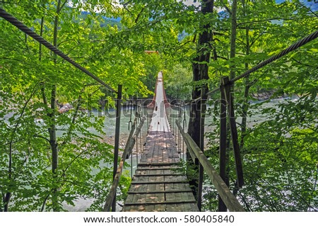 Suspension bridge over the stormy mountain river, the North Caucasus #580405840