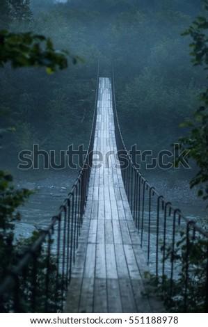 Suspension bridge. Suspension bridge, bridge over a mountain stream. #551188978