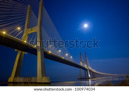 Suspension bridge under moonlight at night - stock photo