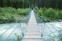 suspension bridge with a wire rope over Landquart river near Monbiel village, switzerland