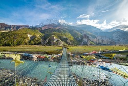 Suspension bridge with buddhist prayer flags on the Annapurna circuit trek in Nepal. Shangri-la land