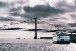 Suspension Oakland Bay Bridge in San Francisco, California, USA. Tourist ferry boat anchoring in port. Landscape in storm. Black and white monochrome view.