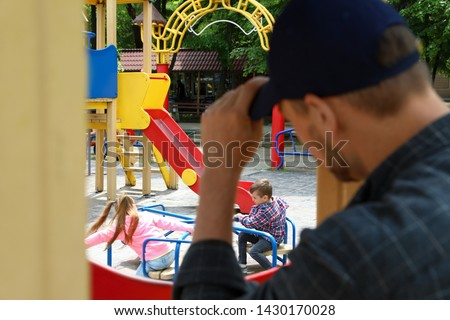 Suspicious adult man spying on kids at playground, space for text. Child in danger
