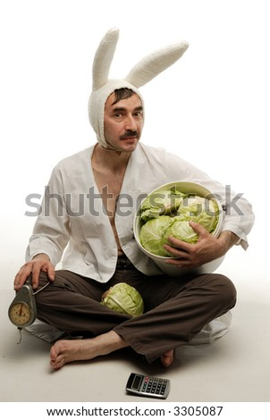 Suspicious bunny sitting hugging basket full of cabbage in one hand and scale in another