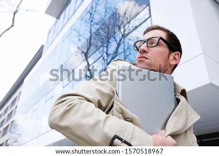 Suspicious businessman carrying laptop under his trenchcoat