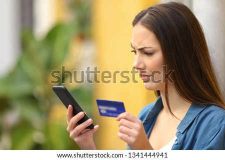 Suspicious buyer buys on line with credit card and smart phone in the street