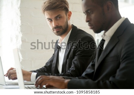 Suspicious cunning male Caucasian worker looking at serious working African American colleague, feeling mad and sneaky distrusting, having doubts, planning. Concept of office relationships, jealousy Stock photo ©