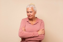 Suspicious elderly woman showing distrustful look at camera. Mistrustful and confused facial expression. Studio shot
