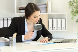Suspicious executive analyzing meticulously a document at office