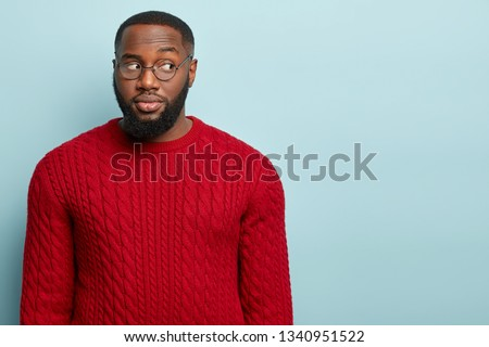Suspicious guy looks away, suspects someone tells lie, thinks doubtful, has thick bristle, wears round spectacles and red outfit, isolated over blue studio wall with empty space for your advert