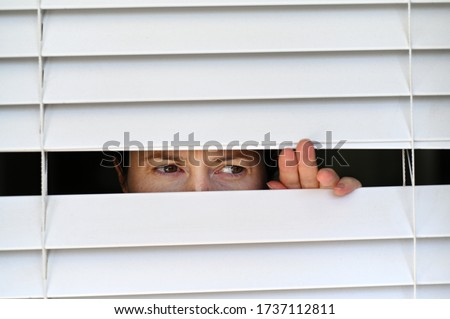 Suspicious person looking outside home window from behind Venetian curtains. Concept photo of person that have Pistanthrophobia and Agoraphobia, a person who don't trust fear of leaving the house.  Сток-фото ©