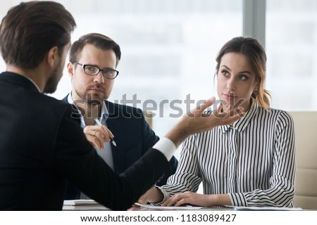 Suspicious recruiters dislike self-confident male job candidate talk at interview, man applicant or employee make bad first impression on HR managers at hiring, failing employment process
