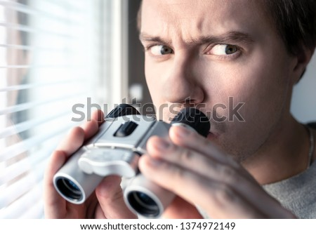 Suspicious, skeptic and confused man with binoculars. Conspiracy theory, paranoia, skepticism or suspicion concept. Curious or paranoid person looking out the window. Mistrustful and nervous guy.