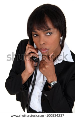Suspicious woman talking on the phone - stock photo