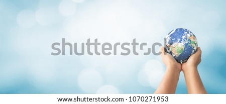 Sustain earth concept: Human hands holding global over blurred blue nature background. Elements of this image furnished by NASA #1070271953