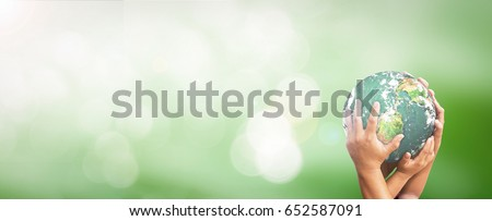 Sustainable development goals (SDGs) concept: People hands holding earth globe over blurred green nature background. Elements of this image furnished by NASA #652587091