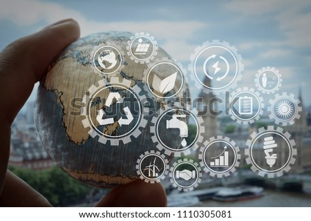 Sustainable development with icons of renewable energy and natural resources preservation with environment protection inside connected gears.businessman hand showing texture the world. #1110305081