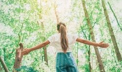 Sustainable eco-friendly fashion clothes woman feeling free with open arms in woods forest happy breating clean air. Travel tourist girl walking in natural healthy environment renewable resources.