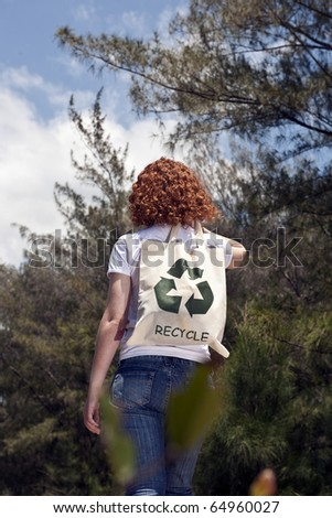 Sustainable lifestyle: Woman with recycling bad in nature