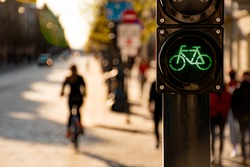 Sustainable transport. Bicycle traffic signal, green light, road bike, free bike zone or area, bike sharing with cyclist and bike on the background