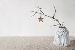 Sustainable, zero waste Christmas natural decoration with white tree branch in macrame vase and wooden Christmas toy star. Xmas simple minimalist elegant design with natural elements. Selective focus