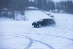 SUV car drifting in snow, during competition, sport car racing drift on snowy race track in winter.