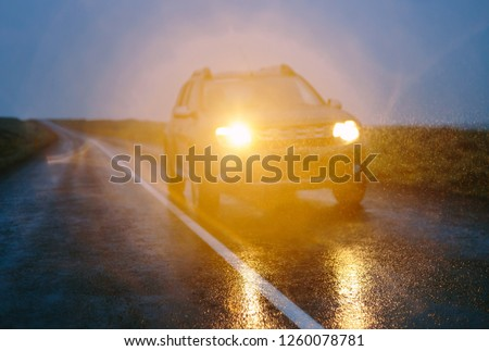 SUV car on wet asphalt road drives in dark rainy conditions. Out of focus countryside landscape with raindrops in the rays of headlights
