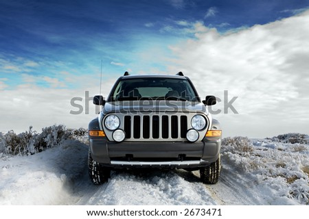 SUV on a rural snowy frosted road, winter sky background
