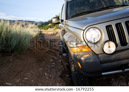 SUV on a trail at the foot of the mountains