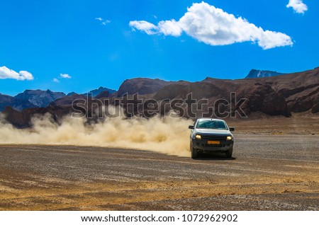 suv raises clouds of dust on a...