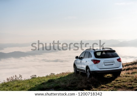 suv vehicle at top of a mountain with clouds on sunset.