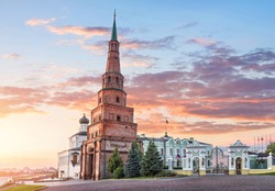 Suyumbike Leaning Tower in the Kazan Kremlin and the Government building with a flag under a pink sunset sky