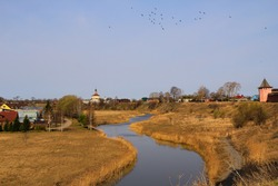Suzdal landscape with views of the Spaso-Evfimiev monastery on the high bank of the Kamenka river, a church and a flock of birds in the blue sky on a sunny April day.