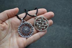 Svarga is a symbol and amulet of the Slavs. Warrior symbol. Medallion on black rope.