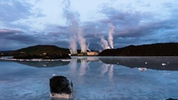 Svartsengi Geothermal Power Plant in Iceland steaming massively with reflection in a blue water of geothermal pool after the sunset and dramatic blue violet sky with thick clouds