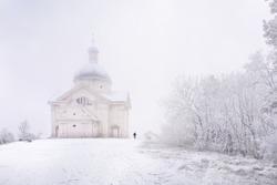Svaty kopecek (Holy hill) - landmark of Mikulov, Czech Republic. Winter scene with father and son on bobsleigh.