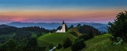 Sveti Andrej, Slovenia - Panoramic view of Saint Andrew church (Sv. Andrej) at sunset in Skofja Loka area with Julian Alps and colorful sky at background. Summer time in the Slovenian alps