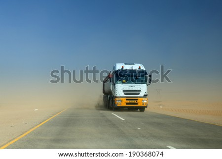 SWAKOMPUND, NAMIBIA - OCTOBER 31 2013: In a year of drought goods vehicle drives through a sand storm through the Namib desert at Swakompmund, Namibia, Africa
