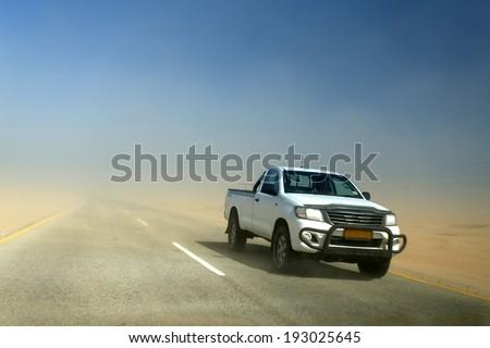 SWAKOMPUND, NAMIBIA - OCTOBER 31 2013: In a year of drought 4x4 vehicle drives through a sand storm through the Namib desert at Swakompmund, Namibia, Africa