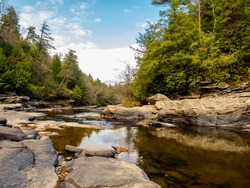 Swallow Falls State Park in Maryland in the fall with the creek bed and rocks in the foreground and the trees and sky in the background.  Beautiful nature in the mountains of Maryland.