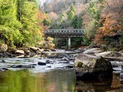 Swallow Falls State Park in Maryland with the water in the foreground, large rocks, and fall foliage trees and a bridge in the background, with colors reflecting in the water.  Beautiful nature.