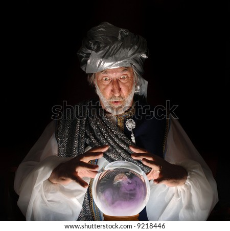 Swami gazing into a crystal ball - stock photo