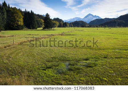 swamp and meadow at autumn with sky, clouds and mountains