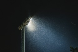 Swarm of bug attracting and flying around light from stadium floodlight at night