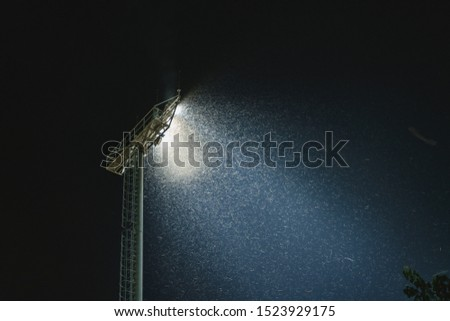 Swarm of bug attracting and flying around light from stadium floodlight at night #1523929175