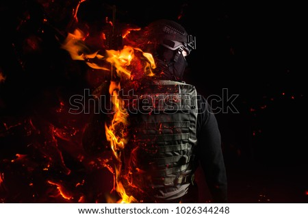 Swat soldier with fire effects. Photo of a swat soldier`s back with flame effect on black background. Foto stock ©