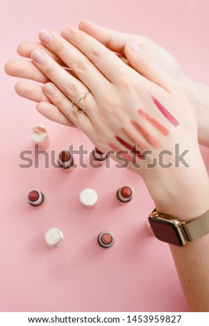 Swatch lipstick on the thin hand of a girl. Swatches of different lipsticks on the background of lipsticks on a pastel pink background #1453959827
